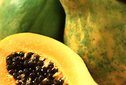 Close up selective focus photograph of a group of Papayas with one cut open