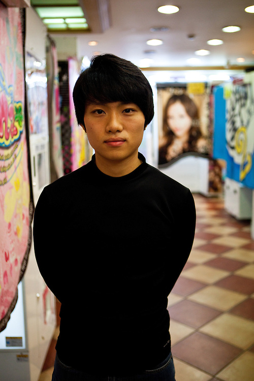 Portrait of a young man working in a kind of photo factory in the city of Daegu. South Korea, Republic of Korea, KOR, 16 October 2009.