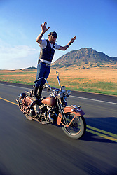 """Puppy and Bear Butte. Sturgis, SD. 1994<br /> <br /> Limited Edition Print from an edition of 50. Photo ©1994 Michael Lichter.<br /> <br /> The Story: I have photographed quite a few bikers surfing like this, but on this occasion and in this frame, Puppy exuded the spirit of what biking is all about as he rides his Flathead past Bear Butte. A friend of mine captured that spirit when she looked at this image and said, """"Feel the Freedom""""."""