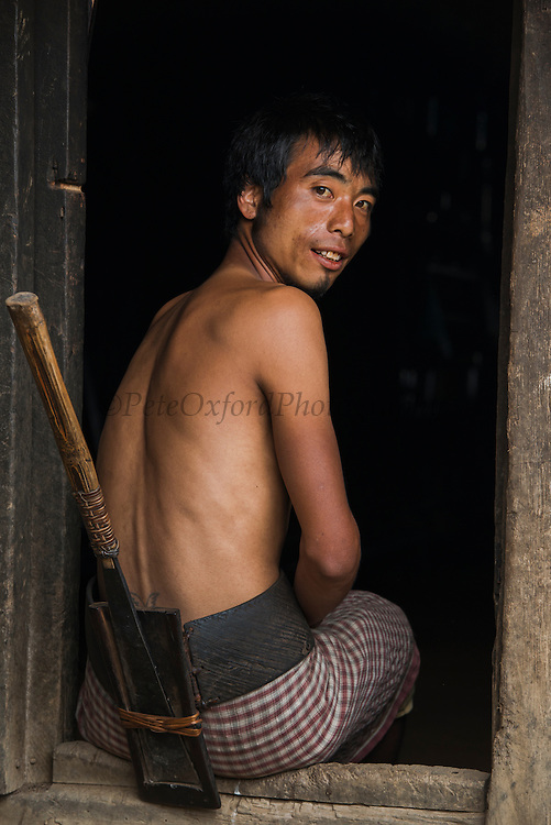 Chang Naga with dao in wooden dao case attached to waist belt. <br /> Chang Naga headhunting Tribe<br /> Tuensang district<br /> Nagaland,  ne India