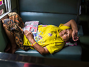 16 APRIL 2014 - BANGKOK, THAILAND: A woman sleeps on her southbound train in Bangkok. They were on a train headed for Sungai Kolok in southern Thailand after coming to Bangkok for the Songkran holiday. Thai highways, trains and buses were packed Wednesday as Thais started returning home after the long Songkran break. Songkran is normally three days long but this year many Thais had at least an extra day off because the holiday started on Sunday, so many Thais started traveling on Friday of last week.    PHOTO BY JACK KURTZ
