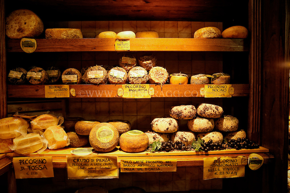 Shelves of decadent cheese in Pienza, Italy.
