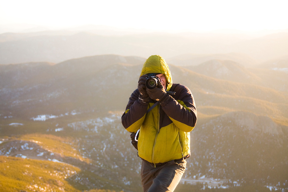 Obadiah Reid takes pictures on the summit of Twin Sisters Mountain at sunrise in Rocky Mountain National Park, Colorado. The rolling hills of the Front Range extend behind him towards the plains.