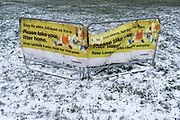 Lambeth council's banner warning against littering, a landscape in a light covering of snow in Brockwell Park, a public space in SE24, south London, on 8th February 2021, in London, England.