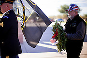 09 DECEMBER 2011 - PHOENIX, AZ:  PETE LINDERT, a US Army veteran of the Vietnam War, carries a Christmas wreath into a wreath laying ceremony at the National Cemetery in Phoenix. Several hundred volunteers and veterans gathered at the National Memorial Cemetery of Arizona in Phoenix Saturday to lay Christmas wreaths on headstones, a tradition started by Wreaths Across America. Wreaths Across America is a nonprofit organization founded to continue and expand the annual wreath laying ceremony at Arlington National Cemetery begun by Maine businessman, Morrill Worcester, in 1992.  PHOTO BY JACK KURTZ
