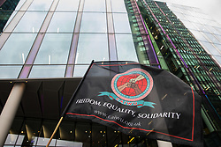 London, UK. 5th August, 2021. A flag is held high by a night-shift cleaner belonging to the Cleaners and Allied Independent Workers Union (CAIWU) during a protest outside the UK headquarters of Facebook. Cleaners are outsourced via the Churchill Group to clean the Facebook offices and CAIWU claims that five additional floors have been added to their workload, that cleaners who have left have not been replaced and that sickness and holiday cover has not been provided.
