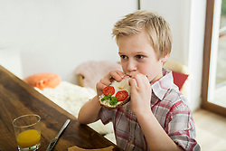 Boy biting off piece of bread and butter