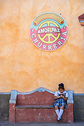 A young Mexican school girl sits on a bench in the town square in the beautiful colonial village of Bernal, Queretaro, Mexico. Bernal is a quaint colonial town known for the Pena de Bernal, a giant monolith which dominates the tiny village is the third highest on the planet.