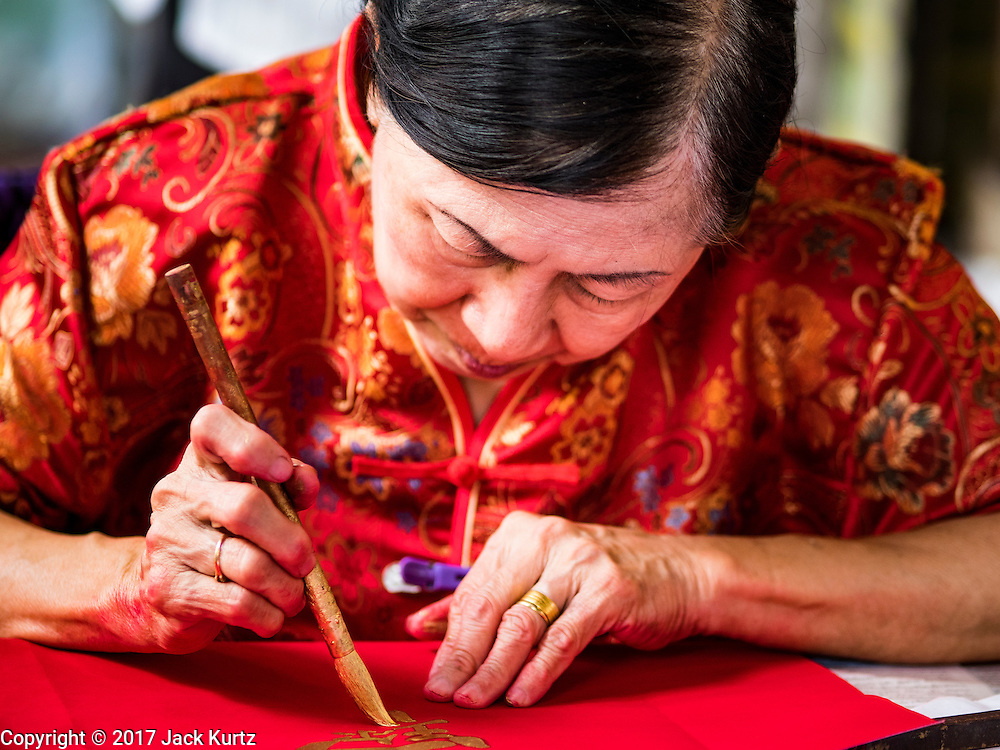 """18 JANUARY 2017 - BANGKOK, THAILAND: A traditional Chinese calligrapher draws New Years greetings that she sells in Bangkok's Chinatown district, before the celebration of the Lunar New Year. Chinese New Year, also called Lunar New Year or Tet (in Vietnamese communities) starts Saturday, 28 January. The coming year will be the """"Year of the Rooster."""" Thailand has the largest overseas Chinese population in the world; about 14 percent of Thais are of Chinese ancestry and some Chinese holidays, especially Chinese New Year, are widely celebrated in Thailand.      PHOTO BY JACK KURTZ"""
