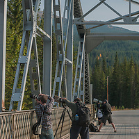 Photographers focus with telephoto lenses from a bridge in Banff National Park, Canada.