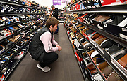 Nicolas Horning, 19, from Anchorage, Alaska, looks for shoes for himself at the Gordman's store in Fairview Heights. He was in town visiting his father who is stationed at Scott Air Force Base. In the background is shopper Alfonso Silva. Shoppers looking for bargains and discounted items endured a light but steady rain on Thanksgiving Day as they waited for stores to open in Fairview Heights, IL on November 28, 2019.<br />  Photo by Tim Vizer