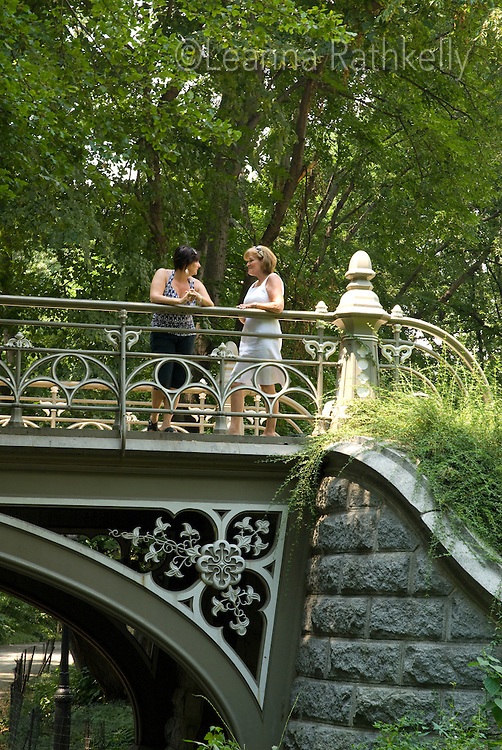 Pam and Carol stop for a chat on one of Central Park's beautiful bridges, New York City, NY, USA