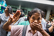 "01 JUNE 2014 - BANGKOK, THAILAND: A woman holds up a three fingered salute and covers her mouth to protest the loss of free speech during a protest against the Thai military coup at Terminal 21 a popular shopping mall in Bangkok. The salute is from the movie ""The Hunger Games"" and symbolizes it admiration, thanks and good-bye to a loved one. In this case, the loved one is reportedly Thai democracy. The Thai army seized power in a coup that unseated a democratically elected government on May 22. Since then there have been sporadic protests against the coup. The protests Sunday were the largest in several days and seemed to be spontaneous ""flash mobs"" that appeared at shopping centers in Bangkok and then broke up when soldiers arrived. Protest against the coup is illegal and the junta has threatened to arrest anyone who protests the coup. There was a massive security operation in Bangkok Sunday that shut down several shopping areas to prevent the protests but protestors went to malls that had no military presence.    PHOTO BY JACK KURTZ"