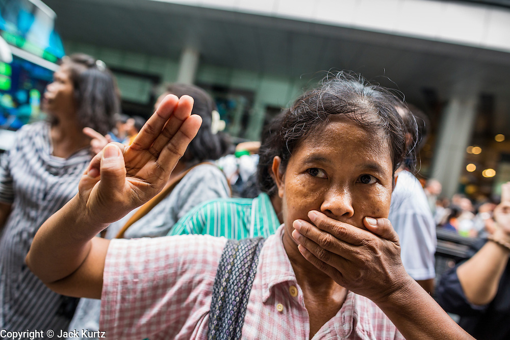 """01 JUNE 2014 - BANGKOK, THAILAND: A woman holds up a three fingered salute and covers her mouth to protest the loss of free speech during a protest against the Thai military coup at Terminal 21 a popular shopping mall in Bangkok. The salute is from the movie """"The Hunger Games"""" and symbolizes it admiration, thanks and good-bye to a loved one. In this case, the loved one is reportedly Thai democracy. The Thai army seized power in a coup that unseated a democratically elected government on May 22. Since then there have been sporadic protests against the coup. The protests Sunday were the largest in several days and seemed to be spontaneous """"flash mobs"""" that appeared at shopping centers in Bangkok and then broke up when soldiers arrived. Protest against the coup is illegal and the junta has threatened to arrest anyone who protests the coup. There was a massive security operation in Bangkok Sunday that shut down several shopping areas to prevent the protests but protestors went to malls that had no military presence.    PHOTO BY JACK KURTZ"""