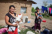 Two young mothers holding their children at the Roma area of Frumusani. Constantin Ionela in the back is 14 years old and has a 6 months old child.