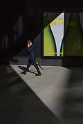 Business person walk through sunlight in the City of London, the capitals financial heart aka The Square Mile, on 26th September 2018, in London, England.