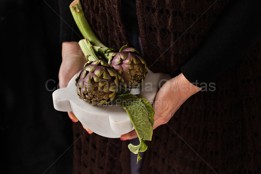 Woman hands holding marble mortar with  fresh artichokes from the garden.