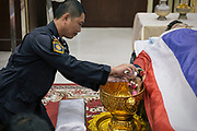 Following violent clashes between police and anti-government protesters, four people died. The funeral of a policeman took place the next day, during which family, friends and colleagues observed traditional bathing rites, pouring water onto the deceased's hand.
