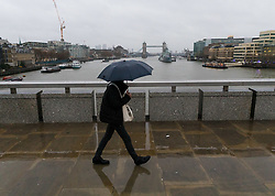 © Licensed to London News Pictures. 01/12/2018. London, UK.  A person walks across London Bridge in front of Tower Bridge with an umbrella during rain and wet weather, near London Bridge on the first day of meteorological winter.  Photo credit: Vickie Flores/LNP on the first day of meteorological winter.  Photo credit: Vickie Flores/LNP