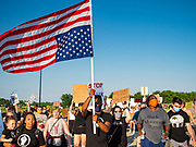 17 JUNE 2020 - NORWALK, IOWA: A member of Black Lives Matter carries an upside down American flag during a Black Lives Matter march in Norwalk. About 400 supporters of Black Lives Matter marched through Norwalk, IA, an upper class suburb of Des Moines Wednesday. Norwalk has a population of about 10,000 and, according to the US Census Bureau, is 97 percent white. The marchers were protesting police violence against people of color. The march was a reaction to the police killing of George Floyd in Minneapolis in May. The march was peaceful.        PHOTO BY JACK KURTZ