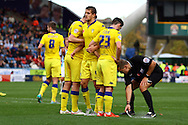 Referee Graham Scott applies the vanishing spray as Leeds players line up their defensive wall. . Skybet football league Championship match, Huddersfield Town v Leeds United at the John Smith's Stadium in Huddersfield, Yorks on Saturday 7th November 2015.<br /> pic by Chris Stading, Andrew Orchard sports photography.