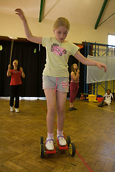 Young girl riding pedalo in school sports hall,