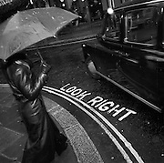 A pedestrian is about to step out across a central London street, crossing the words Look Right as a taxi cab turns left.