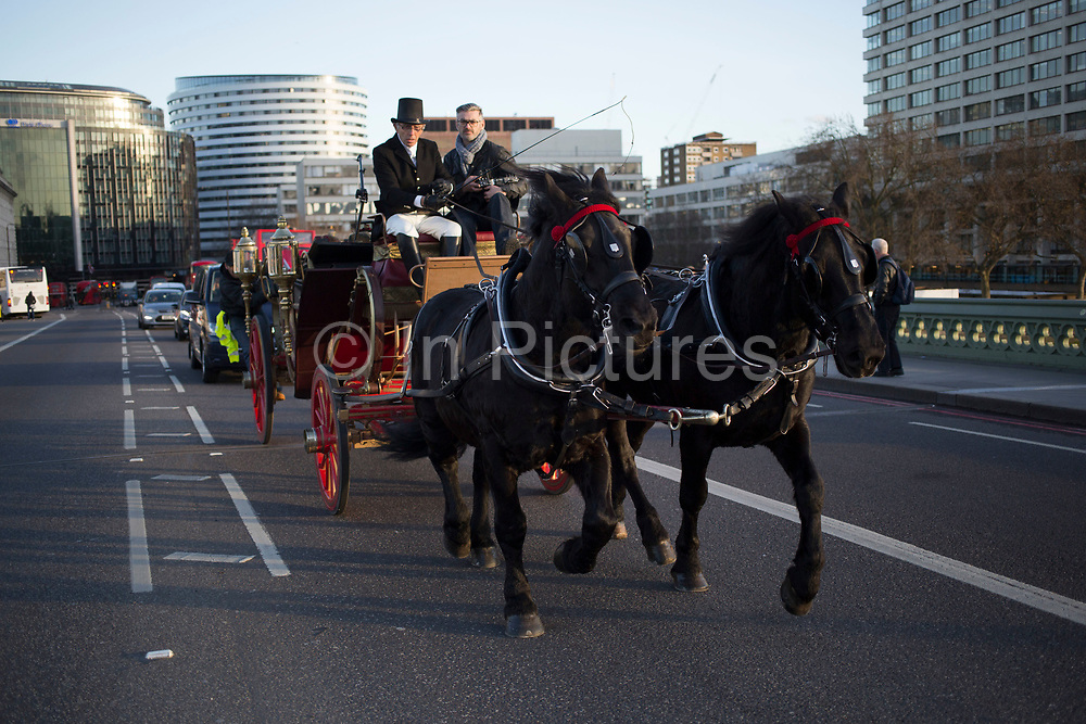 Old fashioned traditional scene as a horse drawn carriage crosses Westminster Bridge, London, UK.