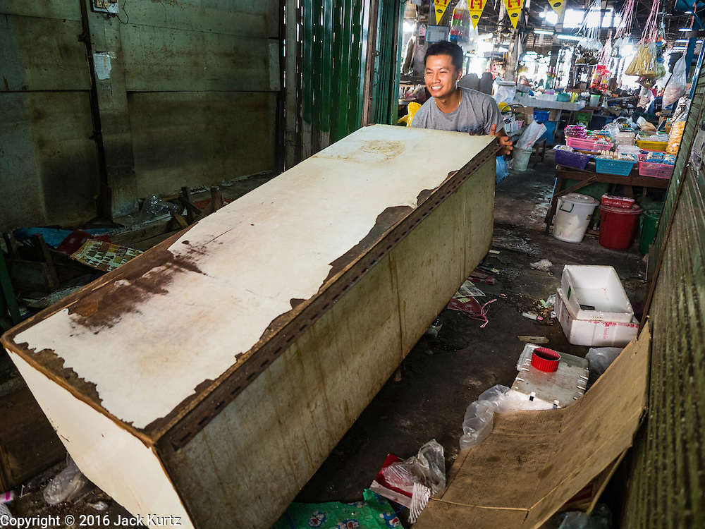 04 JANUARY 2016 - BANGKOK, THAILAND:      A man who owns a shop in Bang Chak Market moves some of his shelving out of the market after he permanently closed his shop. The market closed January 4, 2016. The Bang Chak Market serves the community around Sois 91-97 on Sukhumvit Road in the Bangkok suburbs. About half of the market has been torn down. Bangkok city authorities put up notices in late November that the market would be closed by January 1, 2016 and redevelopment would start shortly after that. Market vendors said condominiums are being built on the land.     PHOTO BY JACK KURTZ
