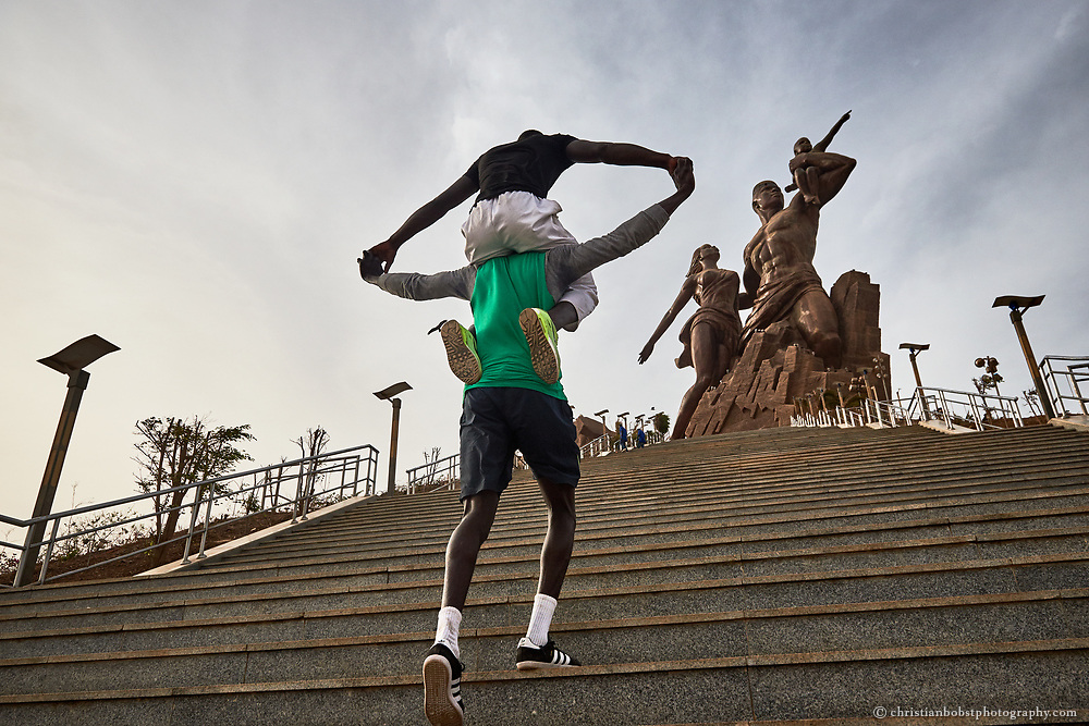 """Kherou Ngor trains on the stair of the """"monument of the African Renaissance"""", with a chummy Wrestler"""