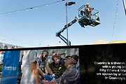 Coventry University hoarding and cherry picker preparations for the a substantial new hub venue in the city centre, Assembly Festival Garden and will be a centrepiece for the city's year of cultural celebrations and will run from 1 July to mid-October for the UK City of Culture 2021 on 23rd June 2021 in Coventry, United Kingdom. The UK City of Culture is a designation given to a city in the United Kingdom for a period of one year. The aim of the initiative, which is administered by the Department for Digital, Culture, Media and Sport. Coventry is a city which is under a large scale and current regeneration.