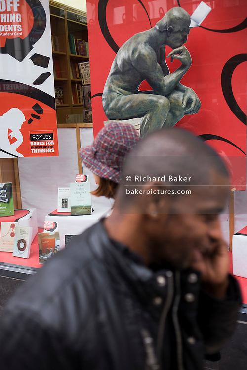 Near Rodin's Thinker poster, pedestrians pass-by Foyles bookshop window outside the shop in London, Charing Cross Road.