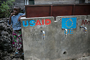 A girl stands next to broken the water stand, Goma, Democratic Republic of the Congo.