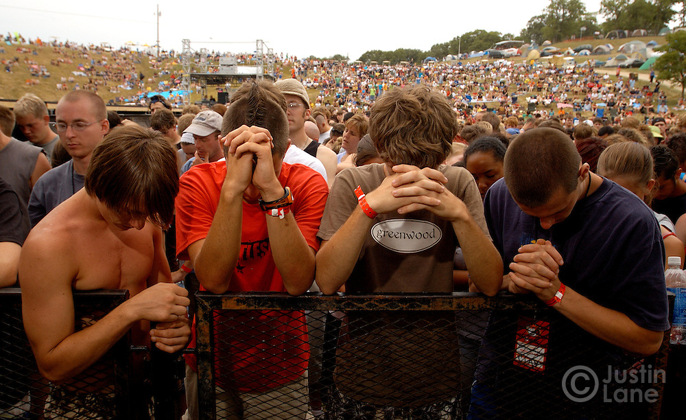 Four teenagers bow their heads in prayer before the start of a rock concert at the 2005 Cornerstone Festival in Bushnell, IL. The festival, which began in 1984, features Christian musicians from across the country and is attended by thousands of people.