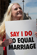 Demonstrators holding placards promoting equal marriage rights outside Parliament in London, UK, ahead of the final reading of the 'Marriage Bill 2012-13 to 2013-14'. A Bill to make provision for the marriage of same sex couples in England and Wales.