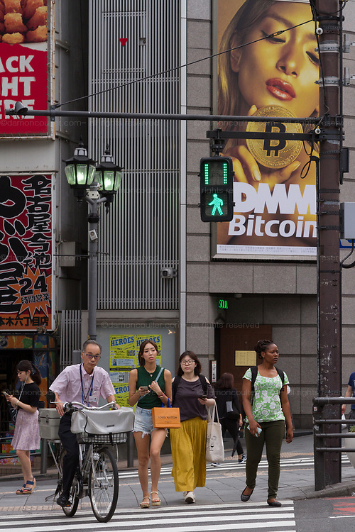 Japanese celebrity Rola advertises Bitcoin trader, DMM on a advertising board above a road crossing in Roppongi, Tokyo, Japan. Friday July 27th 2018