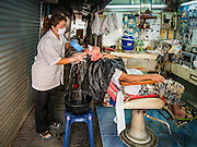 """06 FEBRUARY 2017 - BANGKOK, THAILAND: A barber washes a customer's hair in her small shop in what used to be known as Kalabok Market under the Phra Khanong Bridge in the Phra Khanong district of Bangkok. Kalabok is the Thai word for hairdresser and the market was called Kalabok because there were many barbershops and hairdressers under the bridge. In 1985, the city changed the name of the market to """"Singha Market."""" There are still about 10 small men's barbershops, most with just one barber, and four women's salons, most with one hairdresser,  under the bridge.      PHOTO BY JACK KURTZ"""