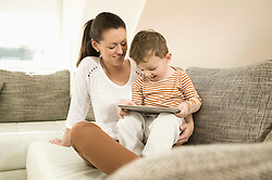 Mother and son using digital tablet in living room, smiling