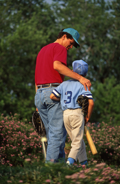 Father and little league baseball son walk and talk.
