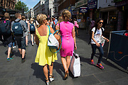 Summertime in London, England, UK. Crowds of tourists and shoppers gather in Leicester Square. This remains one of London's tourism hot spots with entertainers and shop and space to hang out. Two women wearing acid coloured dresses pass through the square towards Covent Garden, where the shopping will no doubt continue.