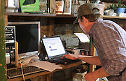 Lou Lenz, brewmaster and owner of the Kaskaskia Brewing Company in Red Bud, checks a laptop computer to verify recipe ingredients and quantities.