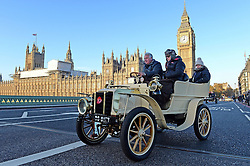 Participants drive along Westminster Bridge past the Houses of Parliament in the Bonhams London to Brighton Veteran Car Run in central London.