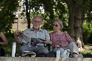 An elderly couple read The Times newspaper in the shade along Richmond riverside as record temperatures soar across England on the 25th July 2019 in Richmond in the United Kingdom. The Met Office has estimated that parts of England could reach a record-breaking 39C this afternoon.