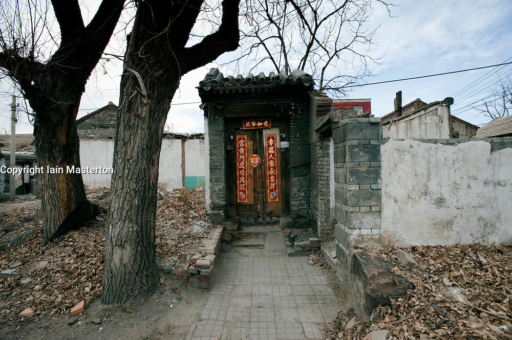 Ornate traditional door to an old house in Beijing a hutong is all that remains after demolition of adjacent houses for redevelopment China 2009