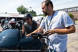Harley-Davidson employee Steven Wells of FL helped Doug McCabe of  Fountain, MN with a Roadglide CVO at the Harley-Davidson test rides out of the Sturgis Civic Center on Lazelle during Sturgis Black Hills Motorcycle Rally. SD, USA. Thursday, August 8, 2019. Photography ©2019 Michael Lichter.