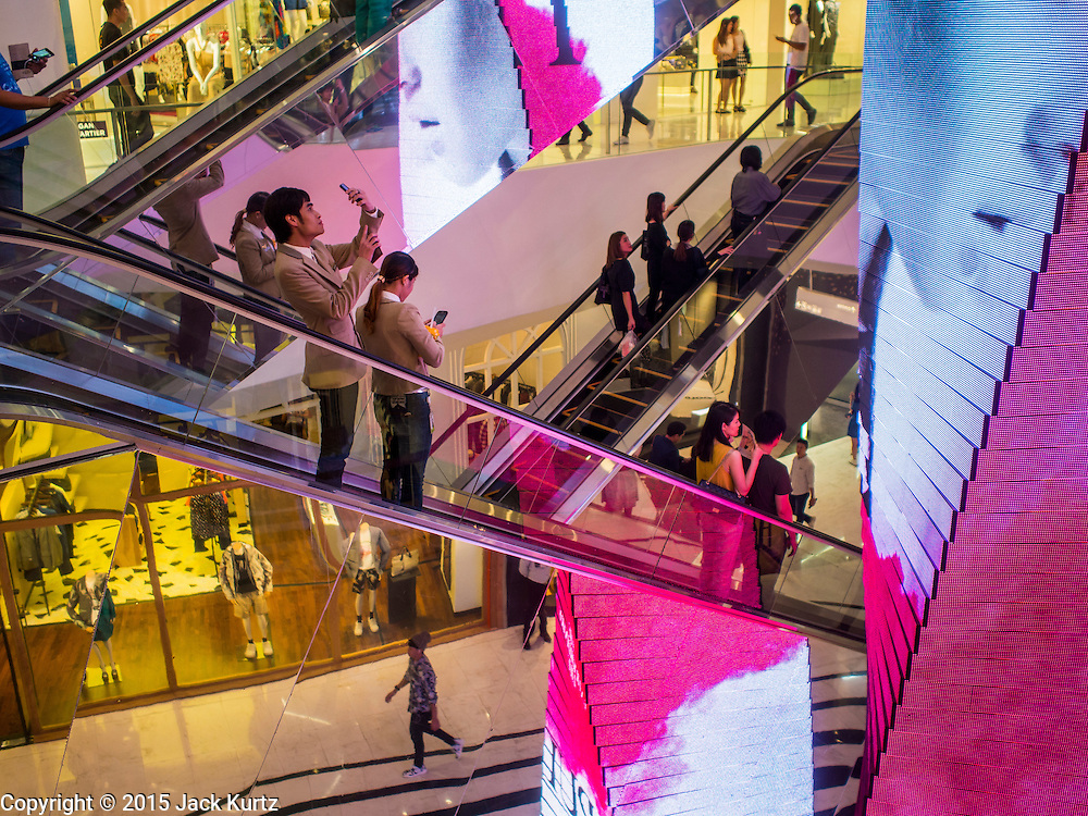 "27 MARCH 2015 - BANGKOK, THAILAND: Shoppers on an escalator in ""EmQuartier,"" a new shopping mall in Bangkok.  ""EmQuartier"" is across Sukhumvit Rd from Emporium. Both malls have the same corporate owner, The Mall Group, which reportedly spent 20Billion Thai Baht (about $600 million US) on the new mall and renovating the existing Emporium. EmQuartier and Emporium have about 450,000 square meters of retail, several hotels, numerous restaurants, movie theaters and the largest man made waterfall in Southeast Asia. EmQuartier celebrated its grand opening Friday, March 27.   PHOTO BY JACK KURTZ"