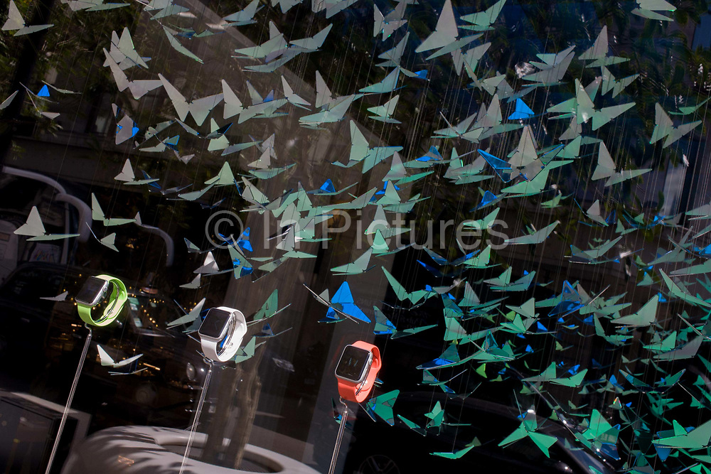 Apple Watches are displayed in a corner window of department store, Selfridges in Oxford Street. Apple has  taken over a corner window display at the London department store, showing off three models to a backdrop of butterflies. A design of in-flight creatures has been installed above the three watches in three colours, a new product from the Apple Corporation - their latest innovation of portable smart devices. Pedestrians walk in the background in this busy street in central London. Selfridges is known for highly-designed, high-profile window displays for the world's best-known brands.