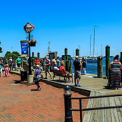 Annapolis, MD / USA - July 9, 2017: People gather along the dock at the harbor on a warm, sunny day in Maryland's capital city.