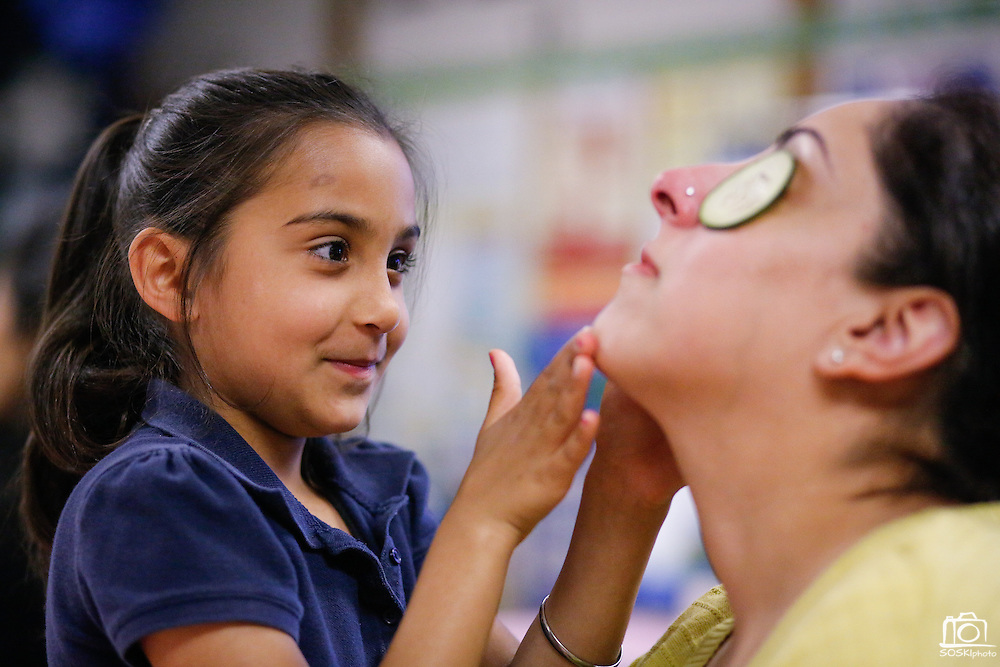 Navleen Hothi, 7, massages her mother, Gruprit Kahlon, during the 1st grade Mother's Day Spa Day at Sinnott Elementary School in Milpitas, California, on May 10, 2013. (Stan Olszewski/SOSKIphoto)