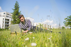 Young man working on laptop and lying in park, Munich, Bavaria, Germany